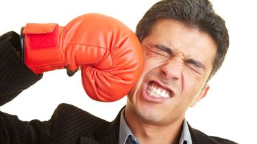 Man punching himself in face with boxing glove