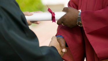 Man shaking hands and receiving university diploma