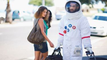 Man walking on street dressed as astronaut