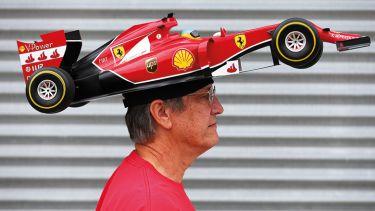 Man with F1 car on head