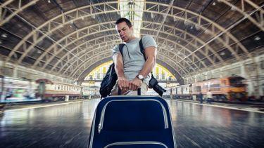 Man dragging heavy luggage