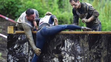 Men helping woman to climb obstacle