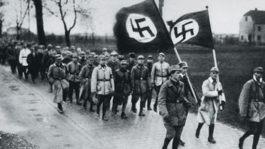 Men marching behind flags with swastikas on them