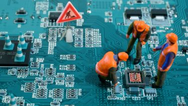 Figures of humans stand and squat on a motherboard