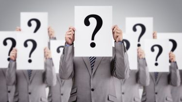 Men in suits holding question marks