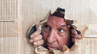 Man peeks through hole in newspaper