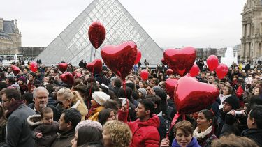 People with red heart balloons outside the Louvre
