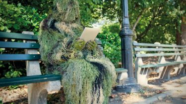 Person in ghillie suit reading on bench
