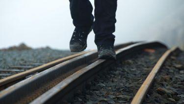 Person walking on rail tracks (detail)