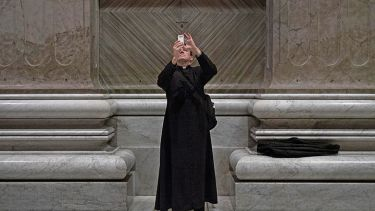 Priest taking photo with smartphone in church