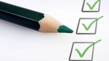 A green pencil beside ticked boxes