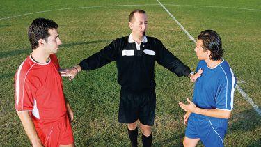 Referee between two footballers