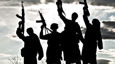 Silhouettes of Islamic terrorists aiming guns at sky