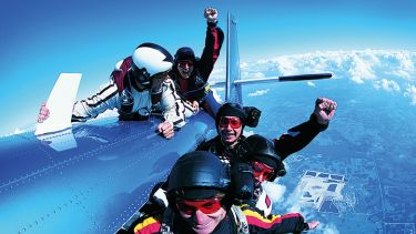 A group of skydivers clinging to a plane