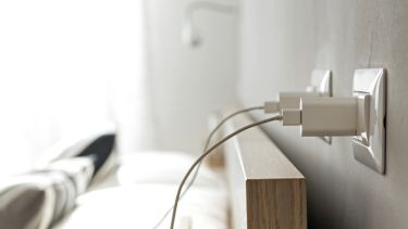 Smartphone chargers plugged into home electrical outlets