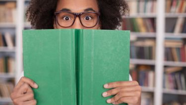 Student peeking behind book, Student Experience Survey 2016 university reviews