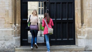Students walking through entrance to Jesus College, University of Oxford