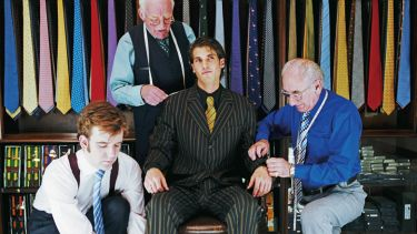 Tailors measuring and adjusting man's suit