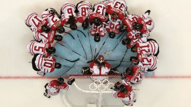 Team Canada in huddle on rink, Winter Olympic Games, 2010