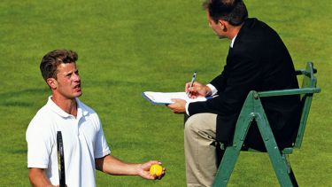 tennis player talks to umpire