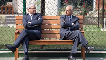 Two men facing each other on a bench