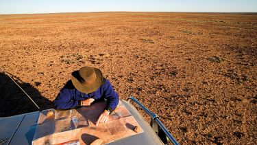 Man reading map on car bonnet in outback. Australia