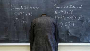 A teacher turned to face the blackboard