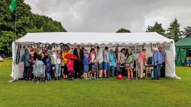 People standing under larger tent to shelter from rain