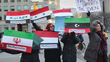 Muslim women hold signs with the flags of the banned countries during a massive protest against President Trump's travel ban outside of the U.S. Consulate in downtown Toronto