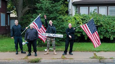 Neo-nazis holding American flag. White supremacists