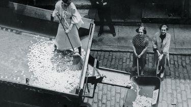 Woman sweeping coins into a wheelbarrow