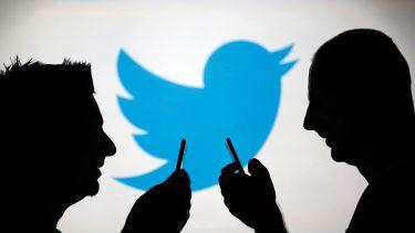 Men using smartphones against Twitter backdrop