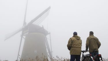 Two cyclists standing in fog looking at windmill