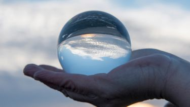 Hand holding a glass globe with a reflection of a sunset