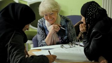 Volunteer tutor instructs asylum applicants in foreign-language class