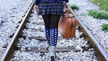 Woman walking alone on railway tracks