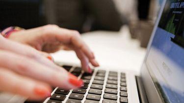 Woman typing Apple MacBook laptop
