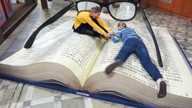 Women lying on giant book