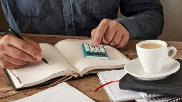 Man writing in a diary with calculator