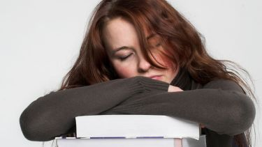 Young woman asleep on pile of books