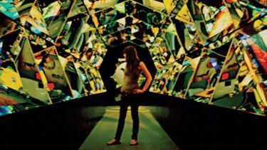 Young woman standing in hall of mirrors