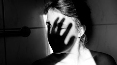 Young woman with shadow of hand over face