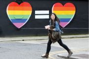 Woman walks past mural in favour of same-sex marriages