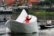 Artist Frank Boelter sitting in life-size paper boat