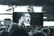 Audience watching opera singer on large screen