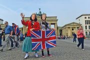 Pair wearing queen masks and holding Union Jack in front of Brandenburg Gate