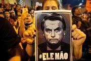 Woman holds poster of Jair Bolsonaro