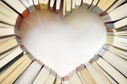 Books arranged on table in shape of heart