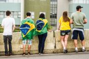 Brazilians with flags looking over wall
