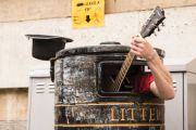 Busker playing guitar in litter bin